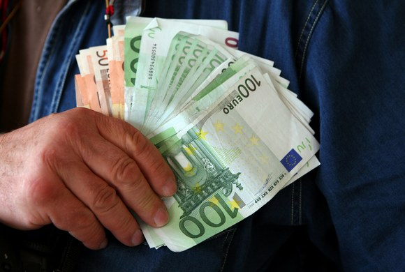 A man with a bundle of Euro notes