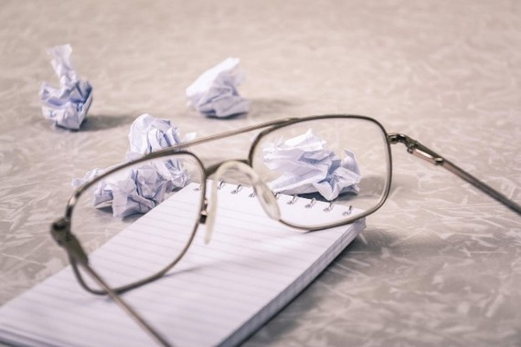 Reading glasses on a notebook, with crumbled pieces of paper