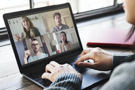 A woman communicating online with 4 people via laptop